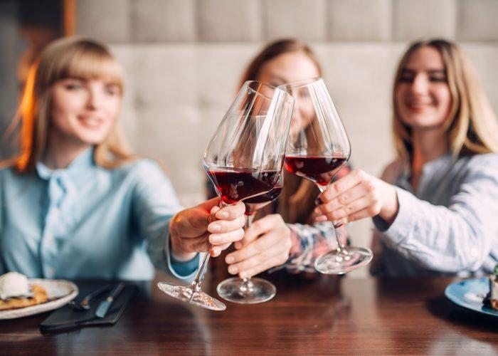 three-girlfriends-holding-beverages-in-glasses-DKJMSXY-min